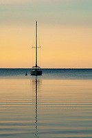 A sailboat is anchored out in Eagle Harbore at dusk in soft evening light, Ephraim, Door County, Wisconsin