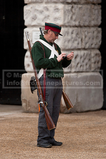 12/06/2012. LONDON, UK. A reenactor of the 'Moscow Militia' uses his mobile phone during a dress rehearsal ahead of the annual Beating Retreat ceremony on Horse Guard's Parade today (12/06/12). Photo credit: Matt Cetti-Roberts
