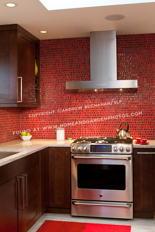 A red tile backsplash provides a vibrant burst of color in this bold, contemporary kitchen remodel. This image is available through an alternate architectural stock image agency, Collinstock located here: http://www.collinstock.com