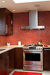 A red tile backsplash provides a vibrant burst of color in this bold, contemporary kitchen remodel.