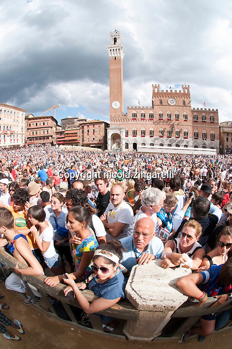 people slowly congregates inside the piazza del campo before the start of the palio di siena. The county's palace and the Torre del mangia shape the background