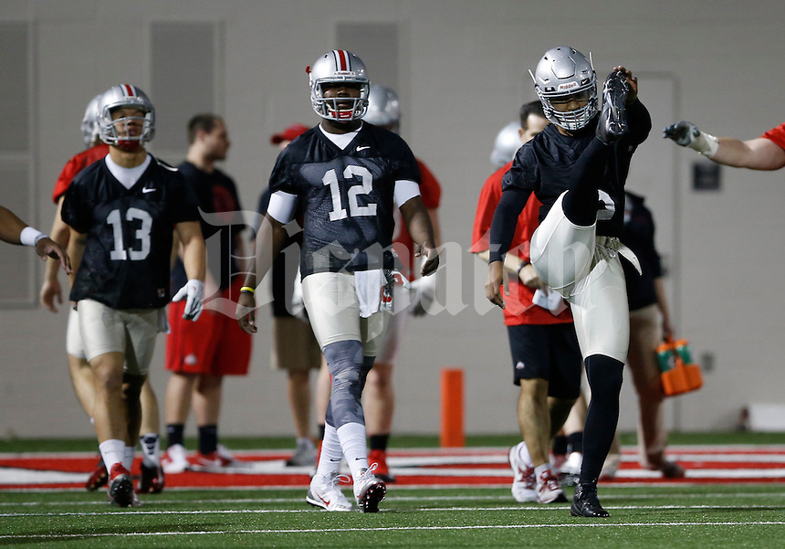 From right, Ohio State Buckeyes quarterbacks Braxton Miller (5), Cardale Jones (12) and Stephen Collier (13) stretch prior to their first practice of spring football at the Woody Hayes Athletic Center on March 10, 2015. (Adam Cairns / The Columbus Dispatch)