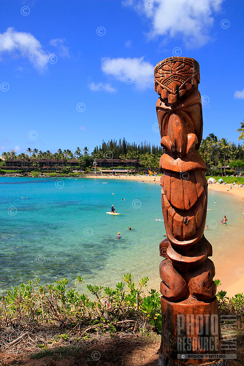A wooden tiki with people enjoying the clear blue ocean at Napili Bay in West Maui.