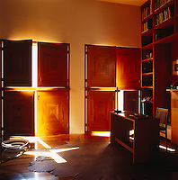 Square shutters made of a tropical hardwood from southern Mexico have been used against the windows of this contemporary study