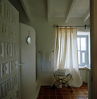A pile of towels on a contemporary metal stool in a whitewashed shower room with a terracotta tiled floor