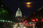 A shrouded full moon rises over the U.S. Capitol.