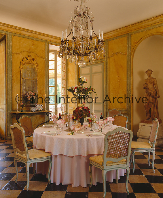 A crystal chandelier hangs above the table  in a dining room with hand-painted boiserie and a black and white stone floor