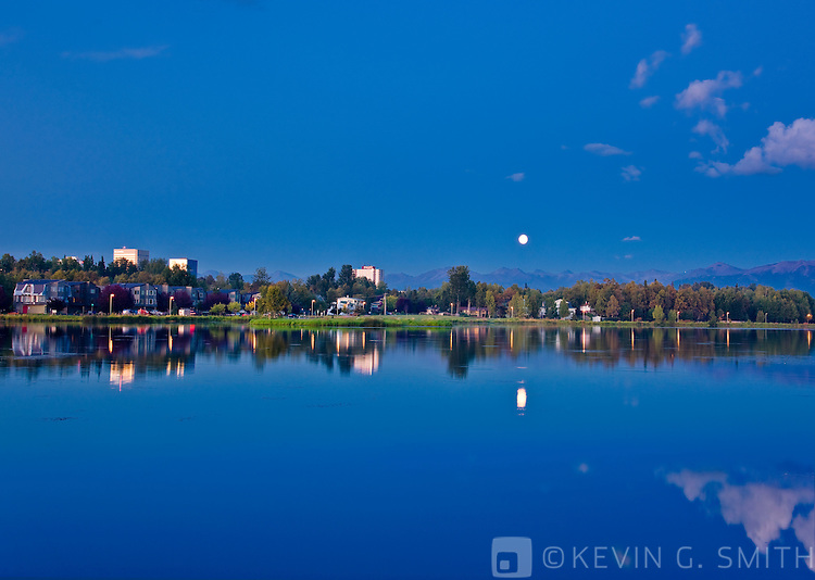 Full moon over Westchester Lagoon, twilight, late summer, Tony Knowles Coastal Trail, Anchorage, Southcentral Alaska, USA.