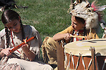 Two Native American Indian children playing the drum and flute