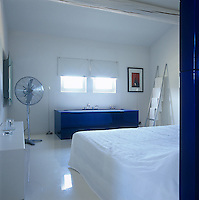 A bathtub encased in blue perspex stands beneath the windows at the end of this bedroom which features a shiny resin floor