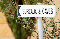 Sign pointing to offices and wine cellar in front of an olive tree.  Chateau de Beaucastel, Domaines Perrin, Courthézon Courthezon Vaucluse France Europe
