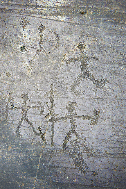 Prehistoric Petroglyph, rock carving, of  warriors with spears shields and a bow carved by the Camunni people in the iron age between 1000-1600 BC, Seradina I rock 12, Seradina-Bedolina Archaeological Park, Valle Comenica, Lombardy, Italy