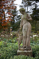 A playful statue of a classical woman and her dog in the garden