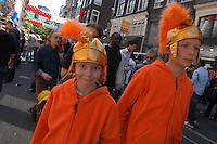 AMSTERDAM-HOLANDA-  Dos jovencitos vestidos de color naranja y casco de guerra durante el día de la Reina./ Two children dressed in orange and old war helmets during the Queen's day.   Photo: VizzorImage/STR
