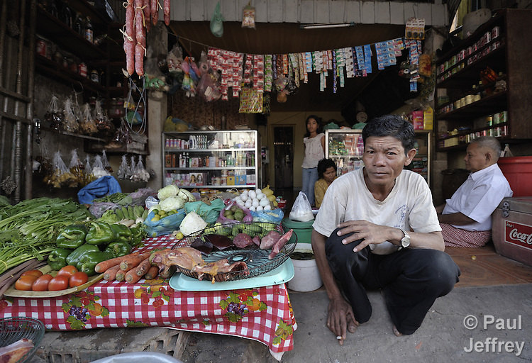 A businessman waits for customers at his vegetable store in the Chamroen neighborhood of Phnom Penh, Cambodia.