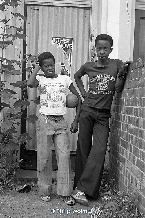 Two boys playing outside an empty and tinned-up house in Bravington Road, North Paddington, London,  1977.