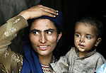 A survivor of the October 2005 earthquake in Pakistan, back home in her mountain village of Khanian after spending months in tent camps at a lower elevation. She and her son still faced innumerable challenges. The quake measured 7.6 on the Richter scale and killed more than 74,000 people in northern Pakistan.