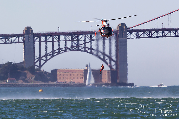 USCG HH-65 Dolphins from Air Station San Francisco lifts a rescu swimmer from the water of San Francisco Bay.