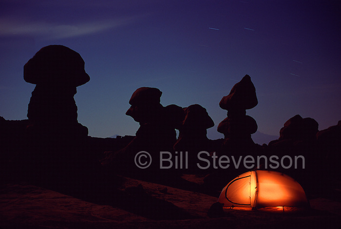 A picture of an illuminated tent at night and strange rock formations in Goblin Valley State Park, UT.