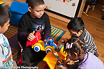 Education preschool 3-4 year olds small group plyaing with vehicles, duplo construction and human figures, one child looking on