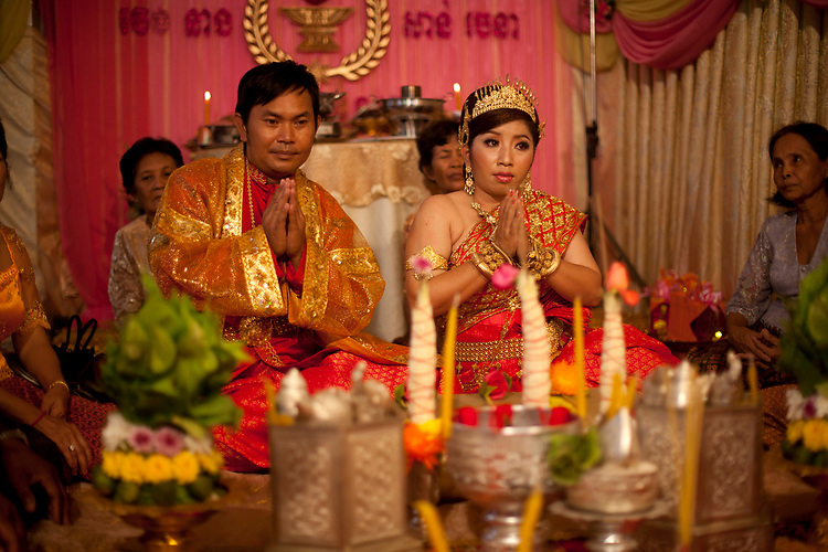 Bride and groom at a buddhist wedding in a small village outside of Phnom Penh, Cambodia. <br /> <br /> Photos &copy; Dennis Drenner 2013.