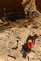 MADAGASCAR, region Manajary, town Vohilava, small scale gold mining / MADAGASKAR Mananjary, Vohilava, kleingewerblicher Goldabbau, Familien graben einen neuen Stollen, KInd spielt mit Ball