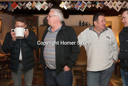 """Wassailers travel around the village of Curry Rivel Somerset on old New Years Eve, January 5th, singing a traditional wassailing song, and bidding the house holders """"... and a happy New Year"""", before being invited in for refreshment.  UK.  2016. Cider punch is served in a Loving Cup to the wassailers."""