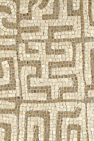 Kuba, a hand-chopped stone mosaic, is shown in tumbled Crema Marfil and Jura Grey.