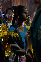 girl watching rituals while Thaipusam ceremonies,  Batu Caves, Kuala Lumpur, Malaysia, 2012. Thaipusam ceremonies, celebrated by tamile Hindu community in Malaysia, take place  in Sanctuary of Batu Caves at the border of Kuala Lumpur, each year around end of January or beginning of February, according to Hindu moon calendar. The event is paying hommage to Lord Murugan, a spirit or god created by Shiva to lead the army of gods against the army of evil demons, finally defeating the evil spirits. There are many ways to present offerings or sacrifices for this major religious event. Devotees mortify their bodies by carrying heavy kavaris with spears fixed in their skin or fruits, flowers and little post with holy milk fixed with hooks in their skin, ascending the stairways to the sanctuary in trance, `followed by assistant  taking care and musicians playing loud and fast rhythmic trance music.  Many families shave their head in a ritual before ascending the stairways, as part of rituals to obtain salvation for their ancestors.