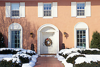 Elegant Rose stucco house Italian style with fresh snow and Holiday wreath of fruit and flowers, Missouri, USA