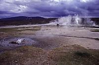 ISLANDA: paesaggio vulcanico. Alcune persone passeggiano tra i geyser che eruttano.