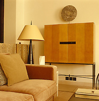 Detail of freestanding cabinet, lamp and corner of sofa in the living area