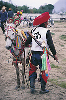 A horseman, in traditional military outfit, with his horse, near Lhasa, Tibet, prepares to enter a race and other tests of his riding skills.