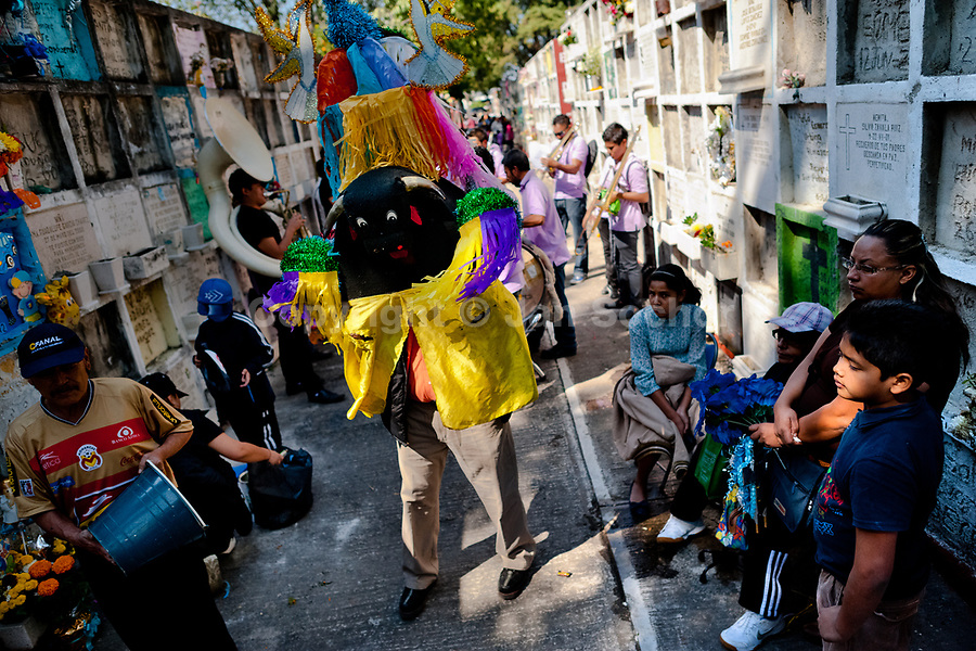 A man wearing a bull costume, accompanied by musicians, performs during the Day of the Dead festivities in the cemetery of Morelia, Michoacán, Mexico, 2 November 2014. Day of the Dead ('Día de Muertos') is a syncretic religious holiday, celebrated throughout Mexico, combining the death veneration rituals of the ancient Aztec culture with the Catholic practice. Based on the belief that the souls of the departed may come back to this world on that day, people gather on the gravesites praying, drinking and playing music, to joyfully remember friends or family members who have died and to support their souls on the spiritual journey.