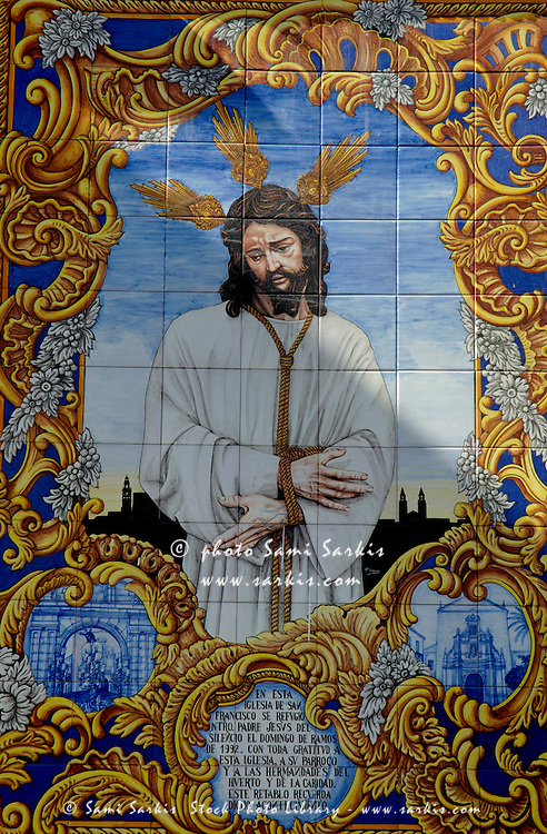 An azulejo ceramic tilework depicting Jesus Christ adorns a building exterior in the Compas de San Francisco, Cordoba, Andalusia, Spain.