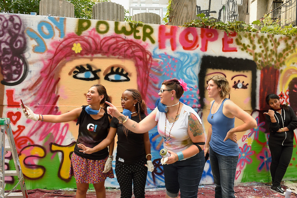 A group of girls taking a selfie in front of the mural.