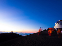 A long exposure image of visitors watching the sun set at the top of Mauna Kea, Big Island.