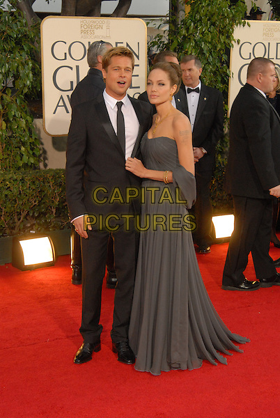 "BRAD PITT & ANGELINA JOLIE.Red Carpet Arrivals - 64th Annual Golden Globe Awards, Beverly Hills HIlton, Beverly Hills, California, USA..January 15th 2007.globes full length strapless grey dress wrap couple black suit tattoo.CAP/AW.Please use accompanying story.Supplied by Capital Pictures.© HFPA"" and ""64th Golden Globe Awards"""