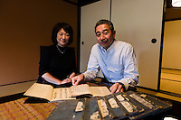 "Tokubee Masuda, CEO of the Tsukinokatsura sake brewery with his wife Kahoru. They are looking at a historic document describing the brewing of koshu matured sake. Fushimi, Kyoto, Japan, October 10, 2015. Tsukinokatsura Sake Brewery was founded in 1675 and has been run by 14 generations of the Masuda family. Based in the famous sake brewing region of Fushimi, Kyoto, it has a claim to be the first sake brewery ever to produce ""nigori"" cloudy sake. It also brews and sells the oldest ""koshu"" matured sake in Japan."