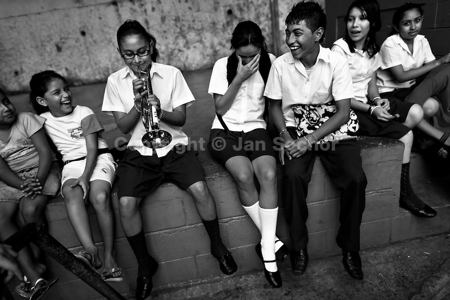 A Salvadorean school girl, sitting among her class mates, plays trumpet in front of the school in San Salvador, El Salvador, 19 May 2011.