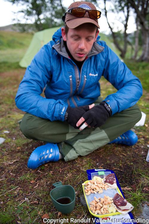 Mann ser lengselfult på brett med fenalår og nøtter. ----- Man waiting for food.