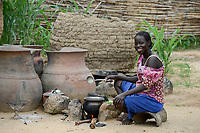 CHAD, Guéra, Bitkine, village Korbo, clay pots for water storage , woman cooks at clay stove/ TSCHAD , Guéra, Bitkine, Dorf Korbo der Volksgruppe Hadjarai o. Hadjerai, Tonkruege als Wasserspeicher, Frau kocht an Feuerstelle