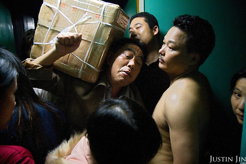 """Migrant workers squeeze into a train in Guangzhou city, China, on their annual holiday back home during Chinese New Year. .This picture is part of a photo and text story on blue jeans production in China by Justin Jin. .China, the """"factory of the world"""", is now also the major producer for blue jeans. To meet production demand, thousands of workers sweat through the night scrubbing, spraying and tearing trousers to create their rugged look. .At dawn, workers bundle the garment off to another factory for packaging and shipping around the world..The workers are among the 200 million migrant labourers criss-crossing China.looking for a better life, at the same time building their country into a.mighty industrial power."""