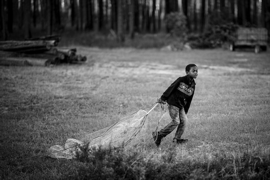 Jamarcus Wilson drags his cast net on his way to try to catch some mullet and shrimp in a creek in the Hog Hammock community on Sapelo Island.