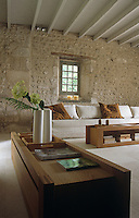 The rustic stone walls provide an ideal backdrop for the clean lines and smooth surfaces of the modern living room furniture