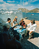 GREECE, Patmos, Diakofti, Dodecanese Island, family and friends dine by the Agean Sea at Diakofti Taverna