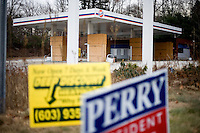 Campaign signs for Texas governor Rick Perry stand outside an abandoned Gulf gas station in Manchester, New Hampshire.  Perry is seeking the 2012 Republican nomination for president.