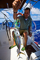 Young sailor with his catch of a small tuna fish caught on green lure in the Molokai Channel, Hawaii