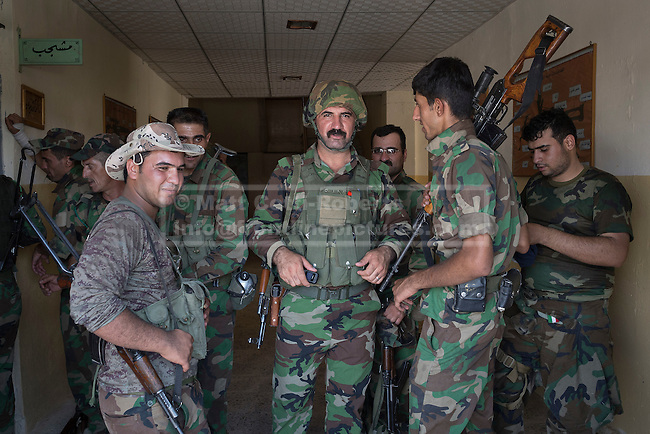 29/06/2014. Khanaqin, Iraq. Kurdish peshmerga stand in the doorway to their barracks in Khanaqin, Iraq, after returning from fighting with ISIS insurgents in nearby Jalawla. Counted by Kurds as part of their homeland, fighting in the town of Jalawla now consists of occasional skirmishes and exchanges of fire between snipers and heavy machine guns on both sides.<br /> <br /> The peshmerga, roughly translated as those who fight, is at present engaged in fighting ISIS all along the borders of the relatively safe semi-automatous province of Iraqi-Kurdistan. Though a well organised and experienced fighting force they are currently facing ISIS insurgents armed with superior armament taken from the Iraqi Army after they retreated on several fronts. &copy; Matt Cetti-Roberts