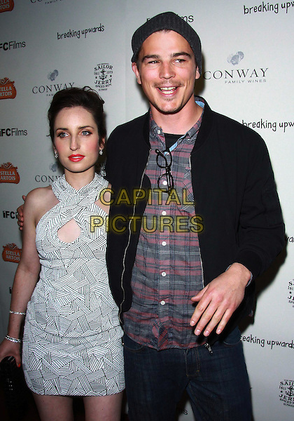 "ZOE LISTER JONES & JOSH HARTNETT .Los Angeles Premiere of ""Breaking Upwards"" held at The Silent Theater, Los Angeles, California, USA, .8th April 2010 .arrivals half length dress  black and white print clutch bag cut out arm around couple beanie hat jacket  trainers plaid shirt checked check hand glasses mouth open .CAP/ADM/TC.©T. Conrad/AdMedia/Capital Pictures."